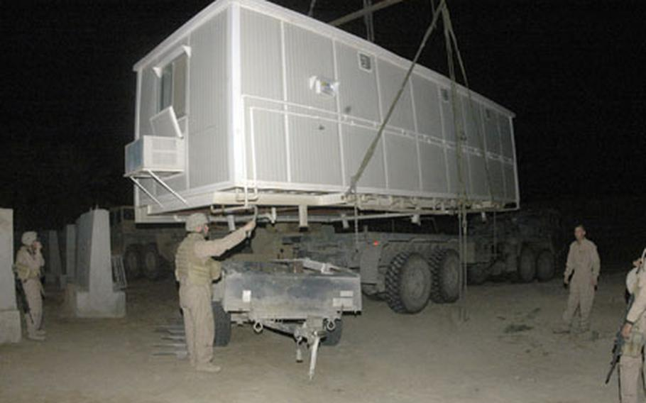 A crane lifts a shower trailer so Marine combat engineers could install it near command headquarter at Out Post 3, in Karmah.
