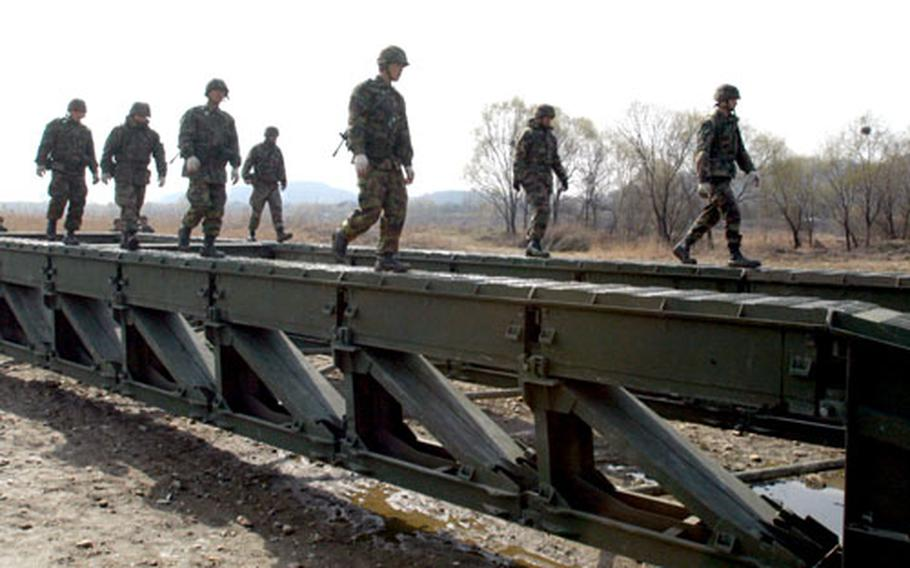 Seabees from the Naval Mobile Construction Battalion 3 and soldiers with the South Korean 1175th Bridge Company cross the framework of a medium girder bridge during an integrated bridging exercise near the banks of the Han River in Seoul on Thursday during the Foal Eagle exercise.