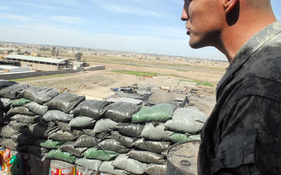 Staff Sgt. Maxwell Davis, 30, of Marfa, Texas, stands on the roof of the Cobra Cabana combat outpost recently, and overlooks a New Baghdad industrial district that commanders hope to revitalize in the coming months.