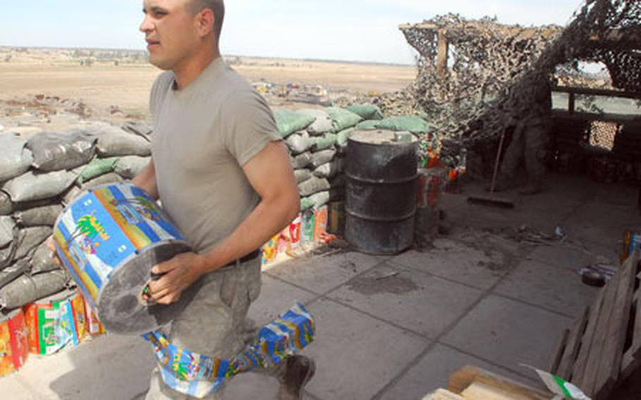 Pfc. Arturo Huerta, 26, of Dinuba, Calif., carries a roll of snack food packaging to add to sandbags reinforcing gun positions atop the Cobra Cabana, a New Baghdad combat outpost that occupies a factory torched by Madhi Army militiamen.