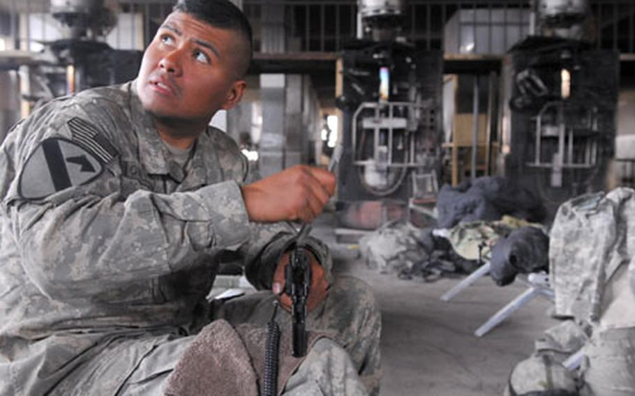 Sgt. Max Orellana, 34, of Silver Spring, Md., cleans his 9 mm pistol during some downtime at the Cobra Cabana, a New Baghdad potato snack factory that was converted into a combat outpost by Company C, 1st Battalion, 8th Cavalry Regiment, attached to the 2nd Brigade Combat Team, 2nd Infantry Division.