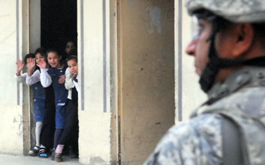 Iraqi school girls wave to soldiers from 1st Platoon, Company D, 1st Battalion, 8th Cavalry Regiment on Sunday. Troops spent much of the day scouting out schools in east Baghdad for potential renovation projects. (The school pictured was not the one where students threw stones at soldiers that day.)