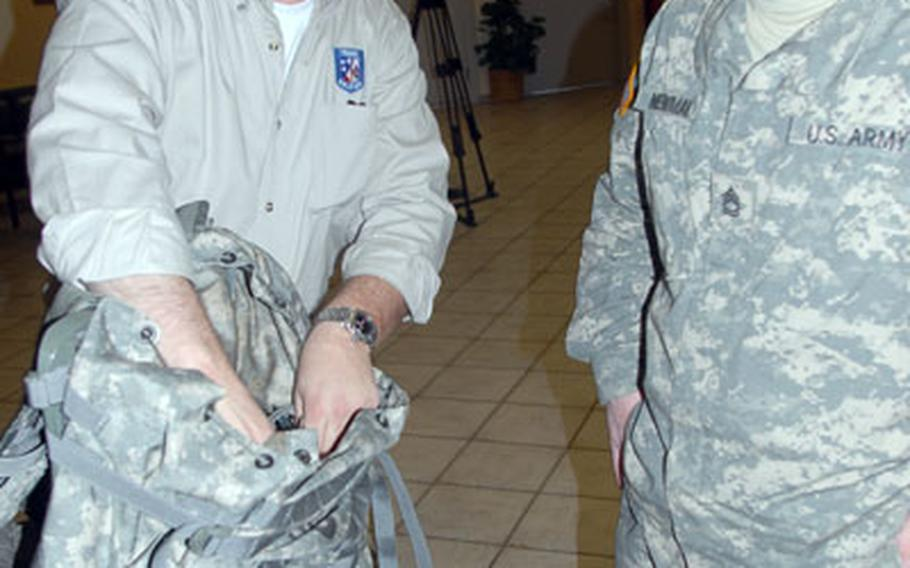 Executive Office Soldier representative Ronald Krakulis, left, shows a new backpack to 2nd Cavalry (Stryker) Regiment soldier Sgt. 1st Class Charles Newman, 29, of Gulfport, Miss.