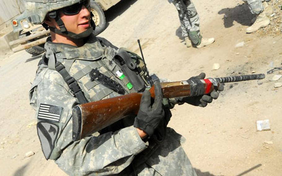 A soldier with Company D, 1st Battalion, 8th Cavalry Regiment holds a rifle stock with a metal pipe taped to it during a recent patrol in the 9 Nissan Security District. The fake weapon belonged to the caretaker of a new housing project who could not afford a real rifle.