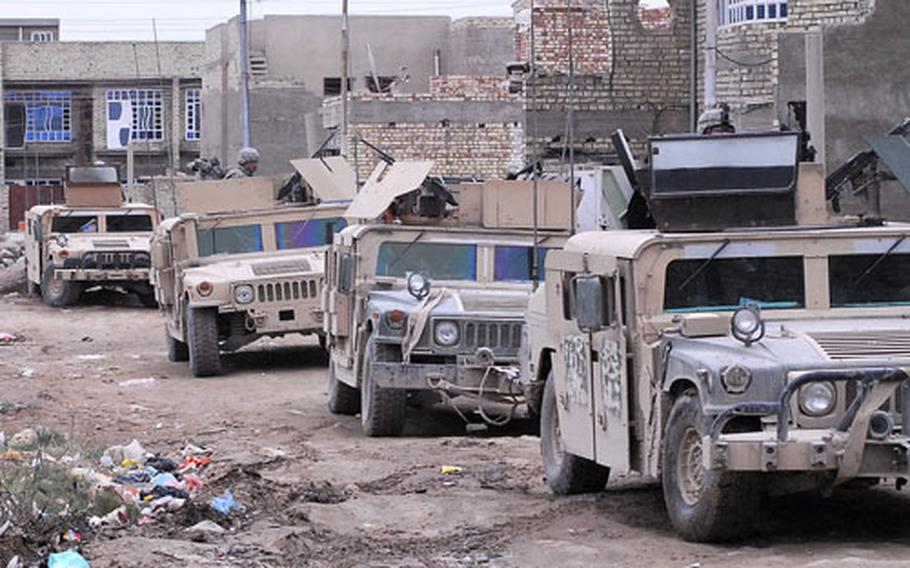 A line of Humvees rolls through a new housing development in the 9 Nissan Security District. Many new and expensive homes have sprung up in former vacant lots in recent months, since the east Baghdad neighborhood is seen as being relatively safe.