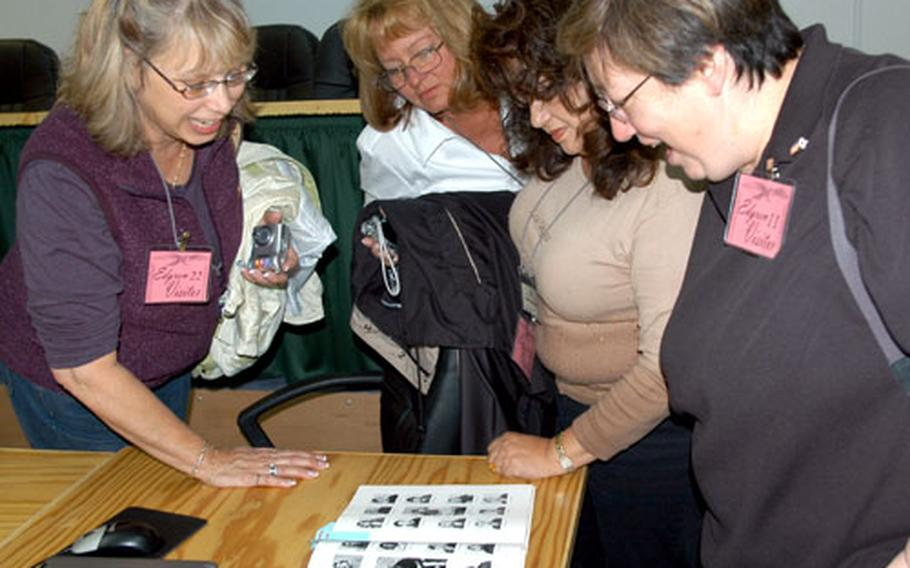 Left to right, Misawa high school alumni Martha Jones, Paula Levitsky Graves, Gloria Rodriguez Crawford and an unidentified classmate, page through a old yearbook while visiting Edgren High School on Monday. Thirteen former students from the late 60s and early 70s came back to their alma mater for the first time in more than 30 years.