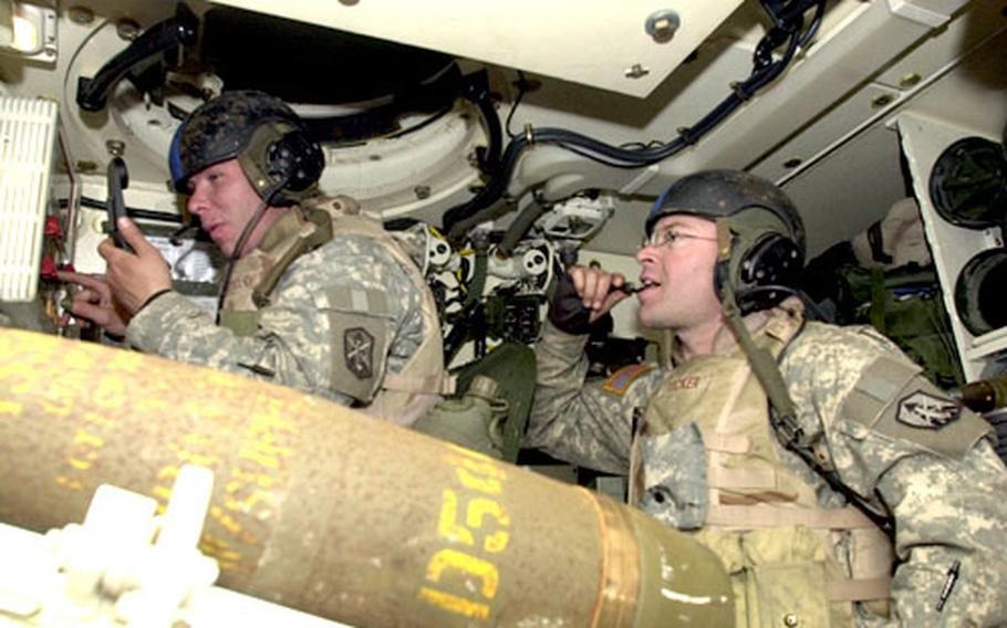Section chief Sgt. Ralph Dobrovolny, left, and gunner Sgt. Rolando Tucker await orders to fire their Howitzer Paladin at a firing point in Jeongok, north of Dongducheon, on Thursday. The soldiers belong to Fort Sill's 2nd Battalion, 5th Field Artillery, Bravo Battery, which is completing its part of the Reception, Staging, Onward movement and Integration exercise.