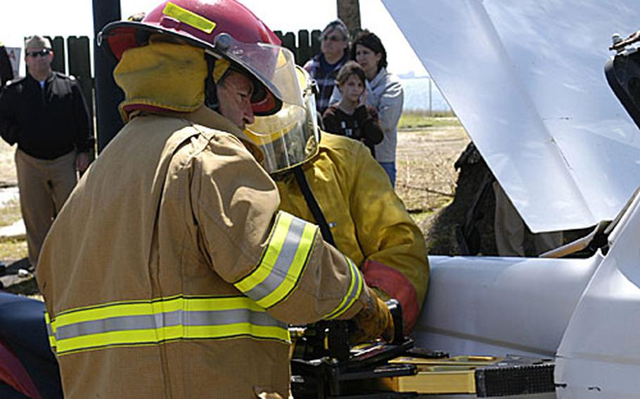 """Alfonso Bernal, a Spainish firefighter, right, and Petty Officer 2nd Class Erik Rosen use the """"Jaws of Life"""" to get a simulated crash victim from a vehicle during the """"Day of the Dead,"""" a project conceived by Rota high school students to promote awareness of the dangers of drinking and driving."""