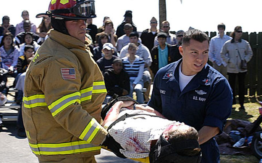 """Petty Officer 2nd Class Russel Armand, left, and Petty Officer 2nd class Dan Gomez carry a crash """"victim"""" from the scene of a mock accident during the """"Day of the Dead."""""""