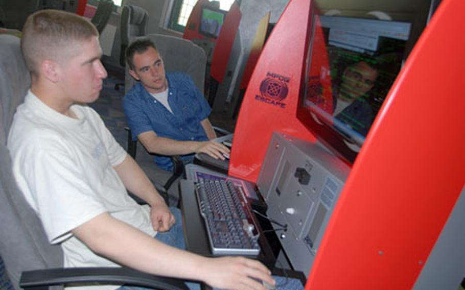 Pfc. Lee Serna, 20, of Corcoran, Cal. (left) and Pfc. Jeff Kempton, 21, of Green Bay, Wis. check out the new multi-player online gaming -- or MPOG -- systems at Vilseck, Germany, on Friday. Twenty MPOG units, designed by the Army, are in Vilseck's new Java Café coffee shop, which opened at the Langenbruck Center on Friday.