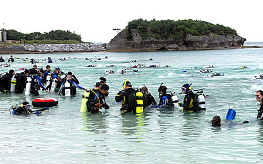 Divers shoot out into the water at Kadena Marina Saturday after the horn signals the underwater Easter egg hunt has begun. Seventy two teams of two participated in the hunt to find the 500 plastic eggs, with numbers inside for a raffle, dropped into the Marina the night before.