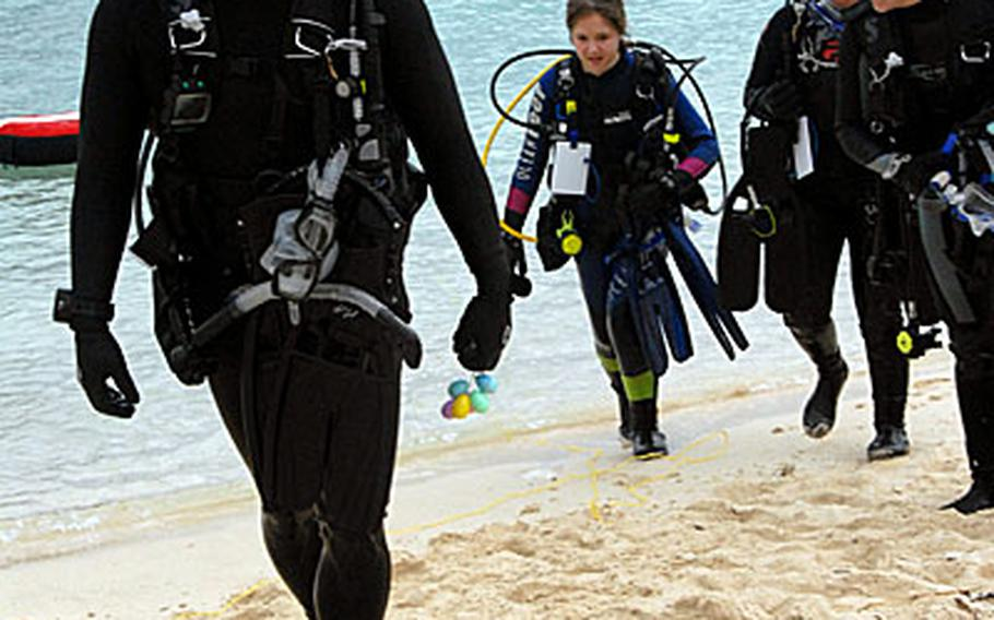"""Marine Master Sgt. Mark Kitashima, of Camp Hansen, comes out of the water after collecting eggs during the underwater Easter egg hunt that 18th Services held at Kadena Marina Saturday morning. """"I wanted to take my daughter out,"""" he said."""