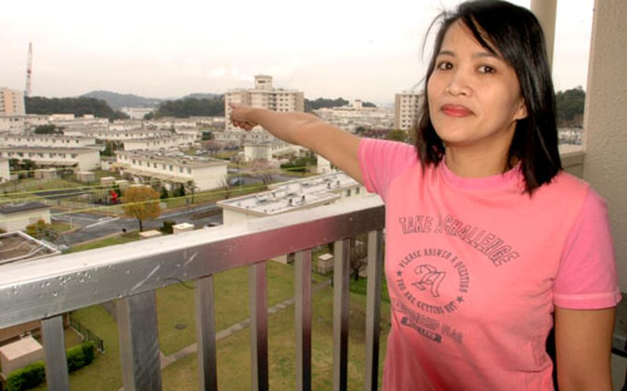 Ellen Angeles, on her Yokosuka Naval Base apartment balcony, points to the Naval Facilities Engineering Command, where she hopes to some day find work as an engineer.