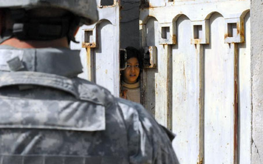 An Iraqi girl in northern New Baghdad peers out the front gate of her home at an American patrol Monday morning.