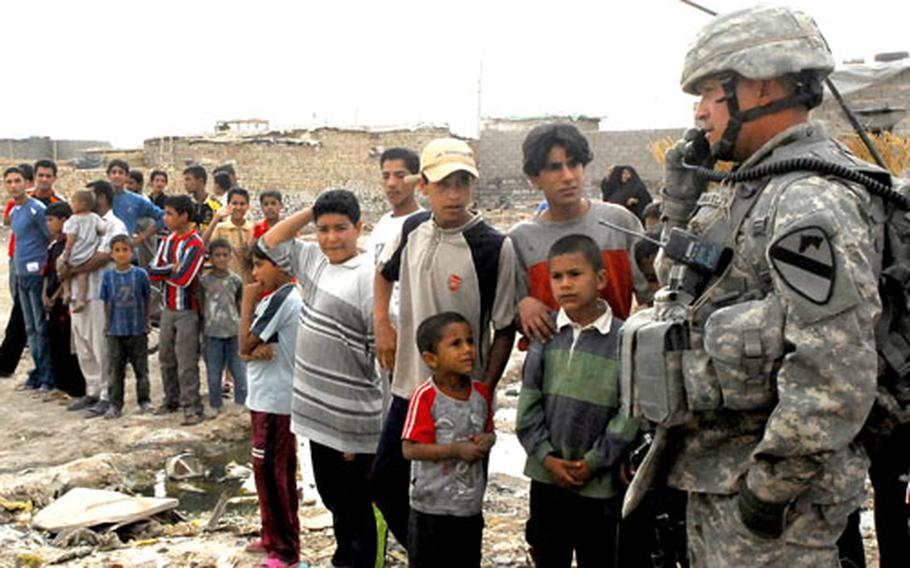 A crowd of Iraqi children forms around Sgt. 1st Class John Wheatley as he radios Company B's command post about a stuck vehicle on patrol Monday.