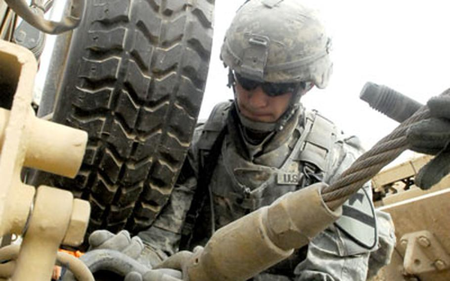 Spc. Krzysztof Socha secures a towing cable to the rear bumper of the stuck Humvee.