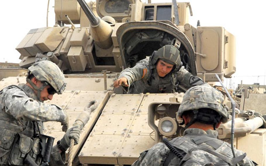 Spc. Krzysztof Socha, left, Pfc. Brit Wooten, inside the Bradley Fighting Vehicle, and Sgt. 1st Class John Wheatley prepare to pull a Humvee out of a mud field Monday.
