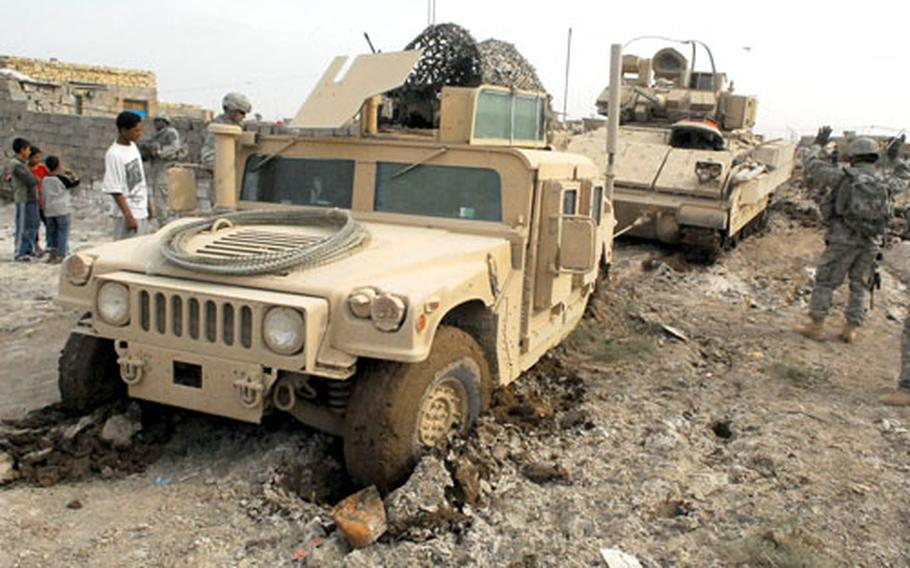 A Bradley Fighting Vehicle uses a towing cable to pull a Humvee out of a mud field on Monday in Baghdad.