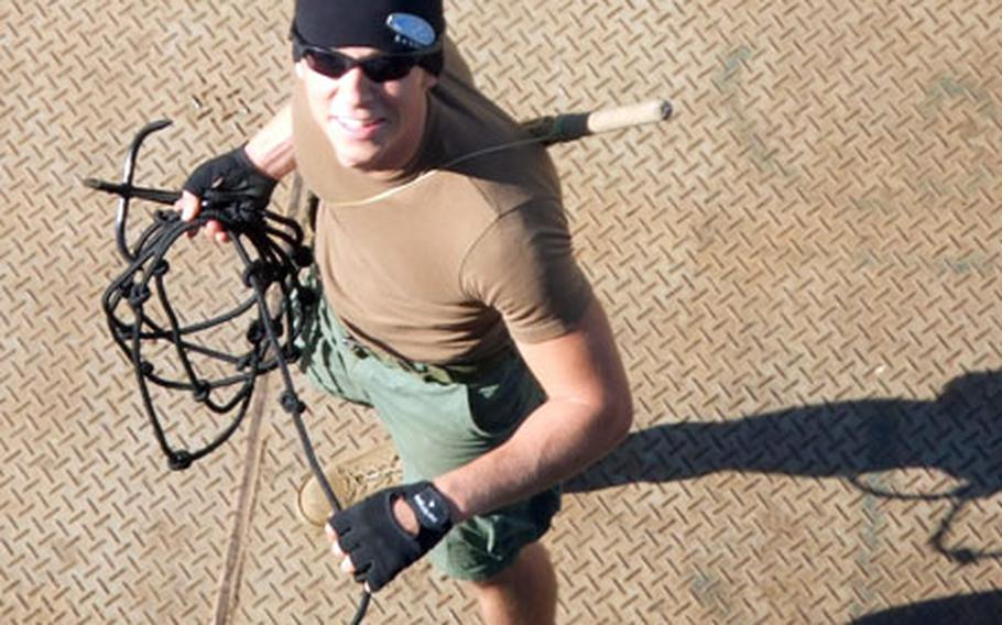 Petty Officer 3rd Class Joshua Fisher, a master-at-arms, prepares to throw a grappling hook as part of training last month for boarding vessels near the Iraqi oil platform Basra in the northern Persian Gulf.