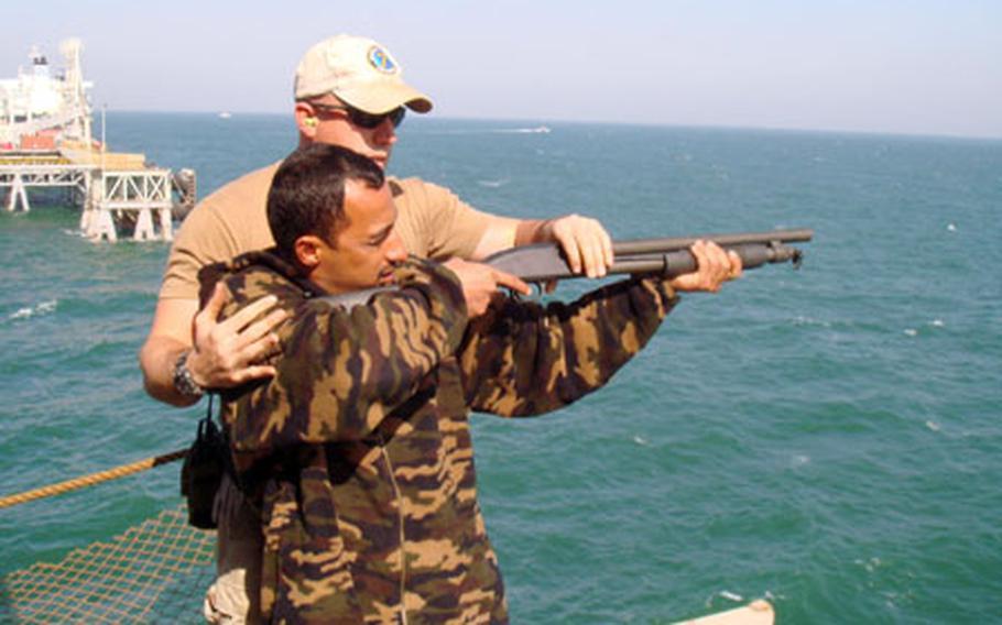 Petty Officer 1st Class John Henklemann, a gunner's mate, instructs an Iraqi marine in weapons handling during an M-500 shotgun training session.
