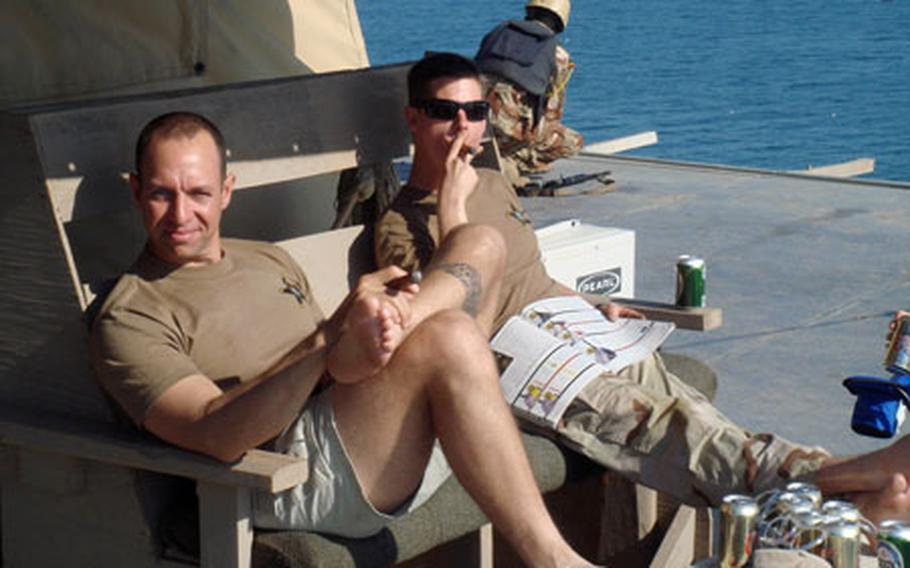 Lt. Aaron Bergman, left, and Petty Officer 2nd Class Christopher Tindell, a master-at-arms, both with Mobile Security Squardon 7, Detachment 73, take a break from duties as an Iraqi marine mans his post in the background on the off-shore Iraqi oil platform Basra. Cigars, non-alcoholic beer and magazines were among the few amenities available on the oil platforms.