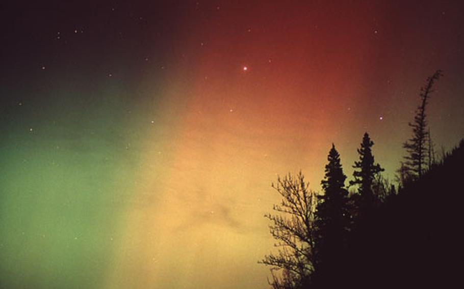 A rare and vivid three-color aurora borealis appears over the Knik River valley in Alaska.