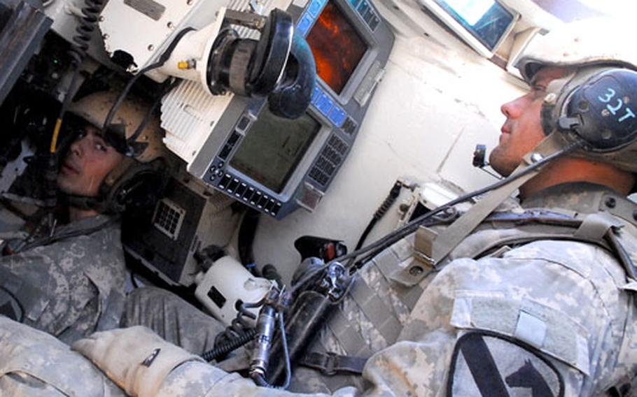 Spc. Jacob Chilcoat, 22, of Baltimore (left), the gunner on an Abrams tank, talks to tank commander Sgt. John Lear, 31, of Fort Meyers, Fla., as their tank rolls through Baghdad. The stretch of road they travel is perhaps the most heavily EFP-laden route in Iraq's capitol, if not the country.