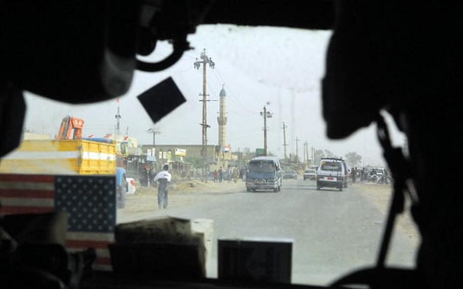 Soldiers in a Humvee drive along a road in northern New Baghdad recently.