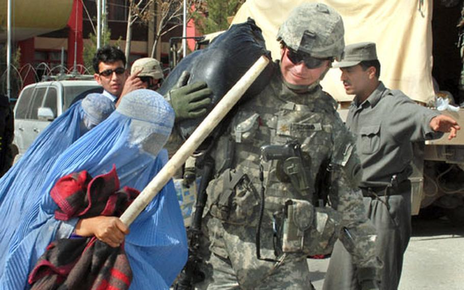 U.S. Army Maj. Arnold Strong, of Task Force Phoenix, assists local Afghan residents with relief supplies.