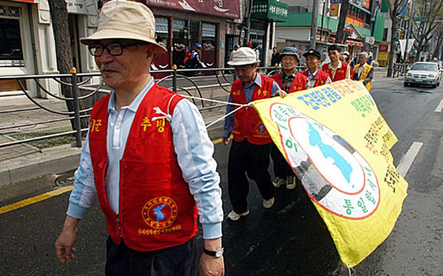 """A small group of anti-American protesters march near Yongsan Garrison while a loudspeaker chants """"Yankee go home"""" on Wednesday."""