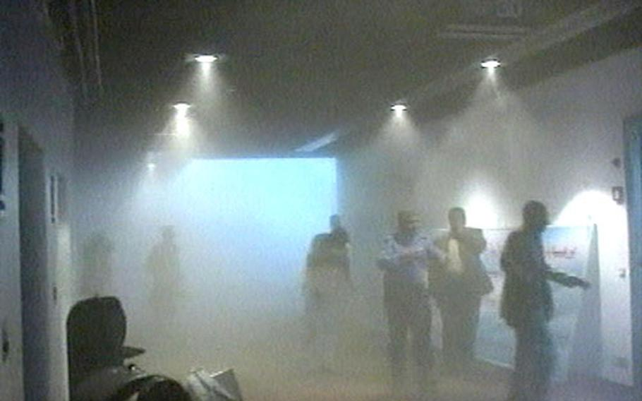 An image from AP Television News shows people leaving the area through thick dust following an explosion in the Iraqi parliament cafeteria within the Green Zone in Baghdad.