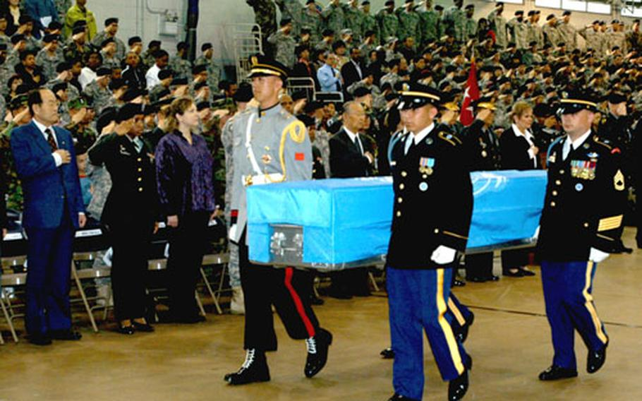 Members of the United Nations Command Honor Guard carry the remains of UNC service members who died in the Korean War to hearses after a repatriation ceremony at Yongsan Garrison's Collier Field House, Thursday.