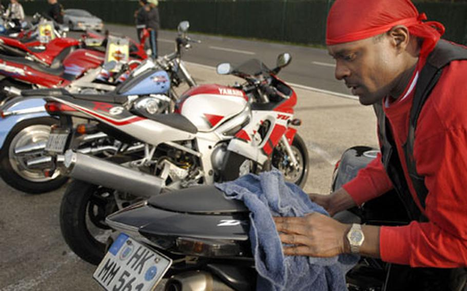"""Master Sgt. Robert """"Smitty"""" Smith, a motorcyclist from Stuttgart, Germany, cleans up his bike Friday after making the long trip in to Kapaun Air Station."""