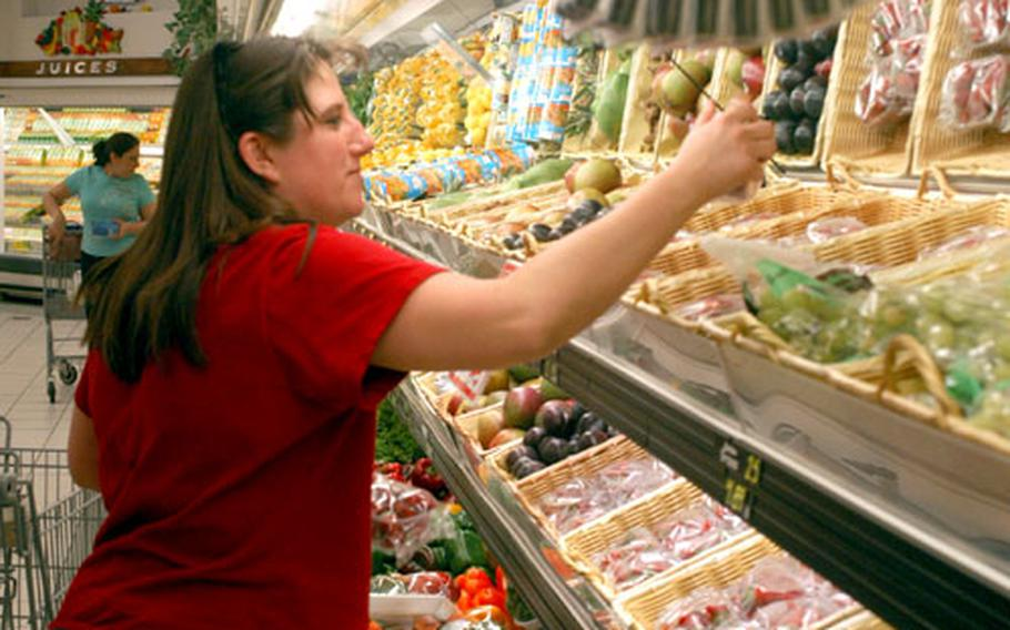 Teresa Dooms selects a few pieces of fruit Monday at the Defense Commissary Agency's store at Aviano Air Base in Italy. Items produced in the States are a bigger bargain on base with the euro rising against the dollar.