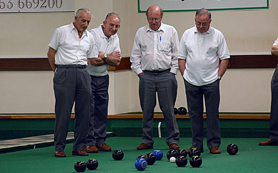 """Members of the Ely Bowls Club watch a wood approach the """"head"""" at a recent league match."""