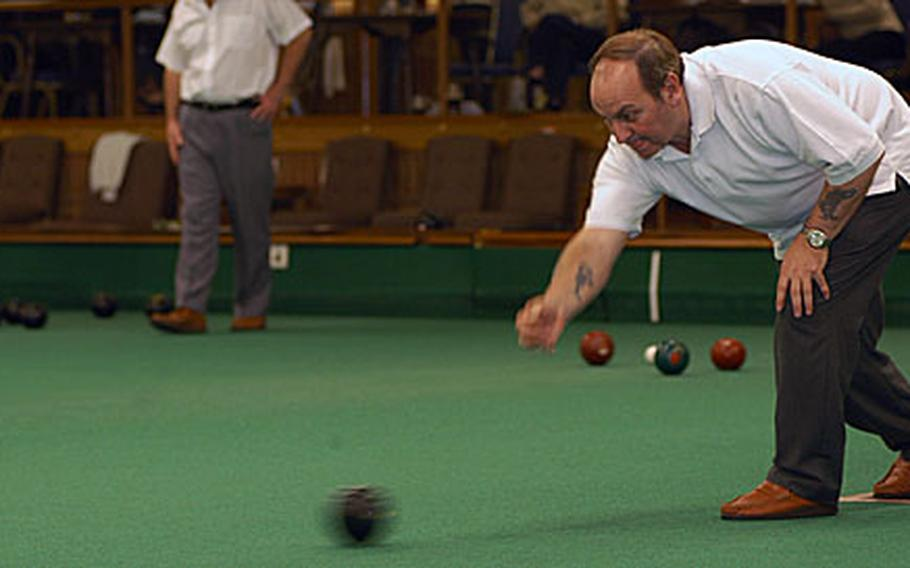 Mick Jordan releases a wood in a Thursday night league match at the Ely Bowls Club's indoor facility. The indoor season runs until late April, when members begin playing outside.
