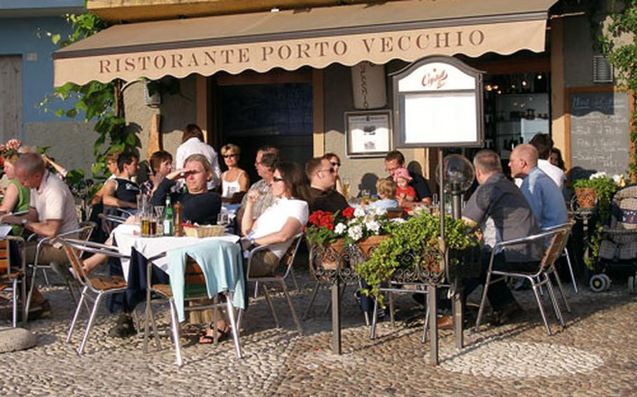 People enjoy the sun and cuisine on Lake Garda at a restaurant on the old port of the medieval town of Malcesine, Italy. According to Cambridge University researchers, Italians are the least happy people in Europe. (enw# 61p rb)