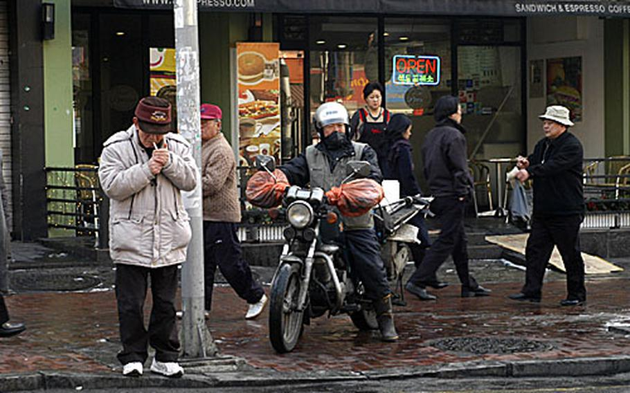 A motorcyclist waits on the sidewalk with pedestrians in Seoul.