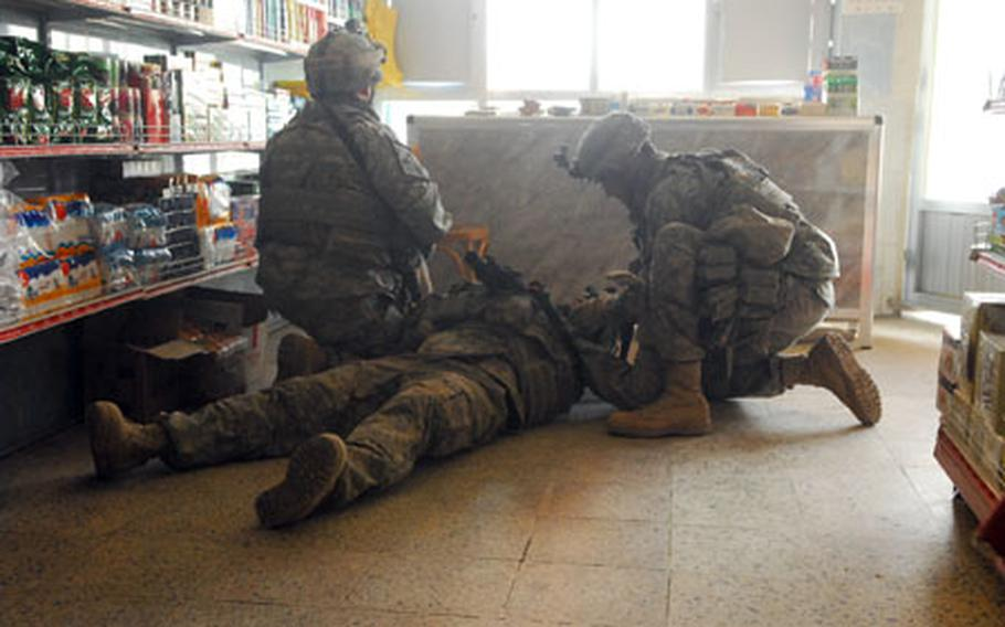 A soldier attached to the 2nd Brigade Combat Team, 2nd Infantry Division, lies on the floor of an East Baghdad market recently after being sprayed by glass from a bullet that shattered the shop's window. The soldier, who at first thought he had been struck, was uninjured. The bullet was either fired by a drive-by gunman or a sniper while the soldiers were on patrol.