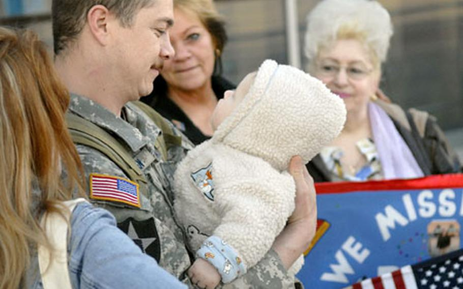 Tech. Sgt. Adam Jensen, a joint terminal attack controller assigned to the 1st Air Support Operations Squadron at Ramstein Air Base, Germany, gazes into the eyes of his 7-month-old son, Cayden, after returning home Saturday from a six-month deployment to Baghdad, Iraq. Jensen is surrounded by his wife, Aljona, foreground, his mother Darlene, center, and his mother-in-law Katerina, right.