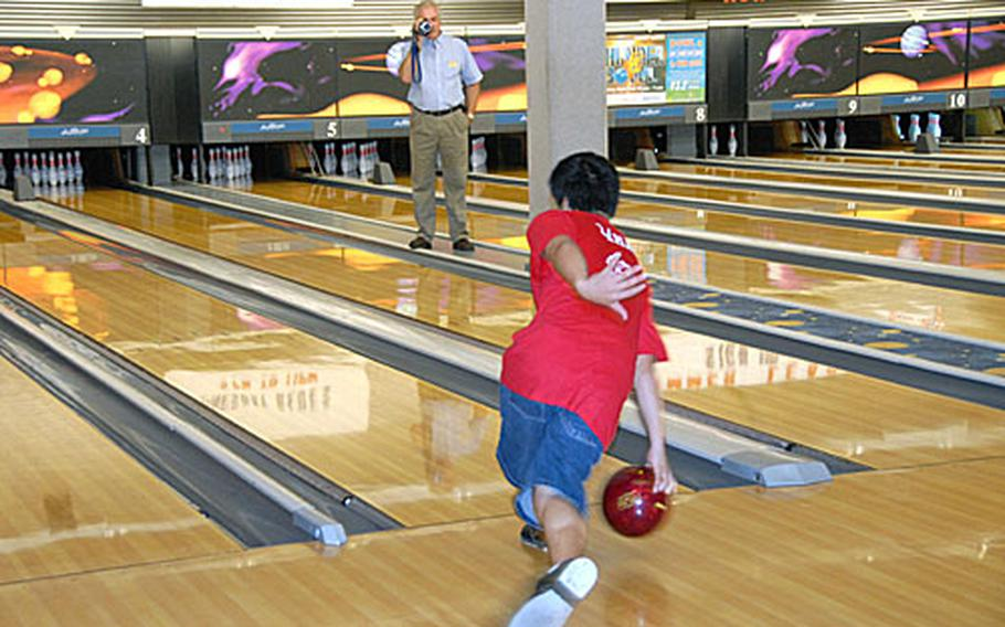 DJ LaMarr practices his strike release during a bowling lesson as his instructor, Ken Miller, video tapes his efforts.