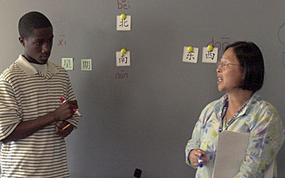 Standing at the blackboard, freshman Isaiah Haines, 14, listens as his Mandarin teacher Su-Lien Reinert tells him what to write.