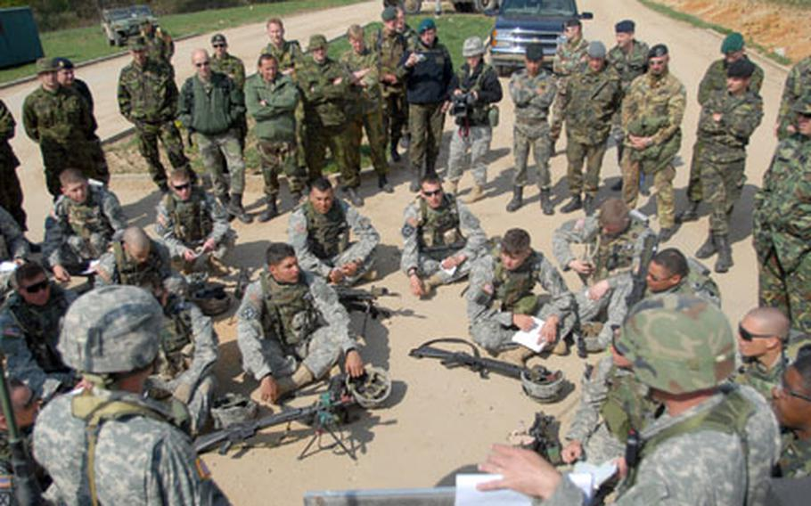 NATO personnel listen in as U.S.soldiers from the 1st Battalion, 4th Infantry Regiment are given instructions during a counter-roadside bomb exercise conducted for the visiting NATO troops at Hohenfels' Joint Multinational Readiness Center on Friday.