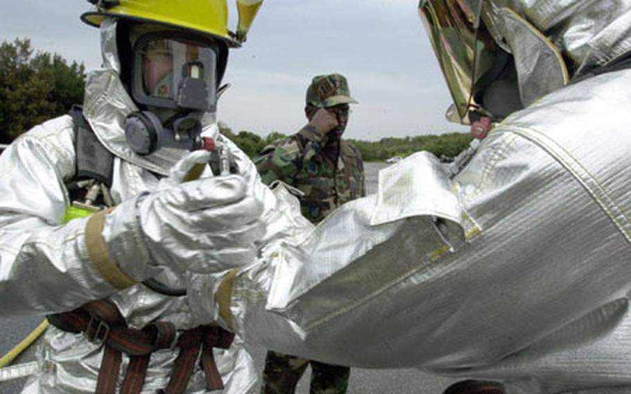 """Airman 1st Class Anthony Fridley, an 18th Civil Engineer Squadron firefighter does a """"buddy check"""" on fellow firefighter Airman 1st Class Tylor Roberts before the two battle a simulated aircraft blaze Tuesday. The check ensures both are correctly wearing safety gear. About 35 airmen participated in the training."""