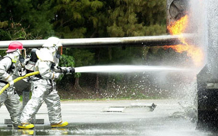 Airmen at Kadena Air Base, Okinawa, direct water to the base of flames shooting from the mock aircraft Monday. Eleven airmen with the 482nd Civil Engineer Squadron from Homestead Air Force Base, Fla., are training with Kadena firefighters until April 30.