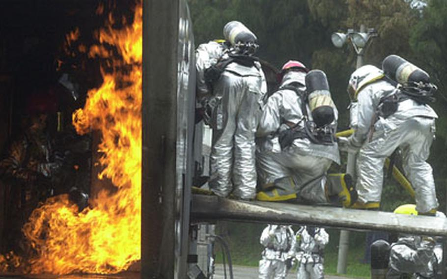 Several firefighters feed a hose to another firefighter as he battles a blaze in the interior of a mock aircraft during an exercise Monday on Kadena Air Base, Okinawa.