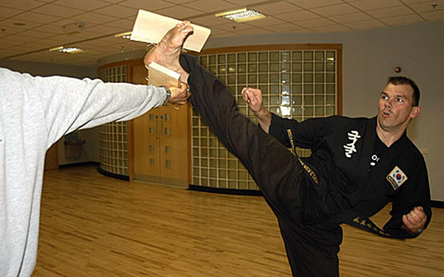 """Martial arts expert and Lakenheath Fitness Center instructor Darrin Hart smashes a board in a demonstration of one of the skills he displayed on """"Britain's Got Talent,"""" a national talent contest."""