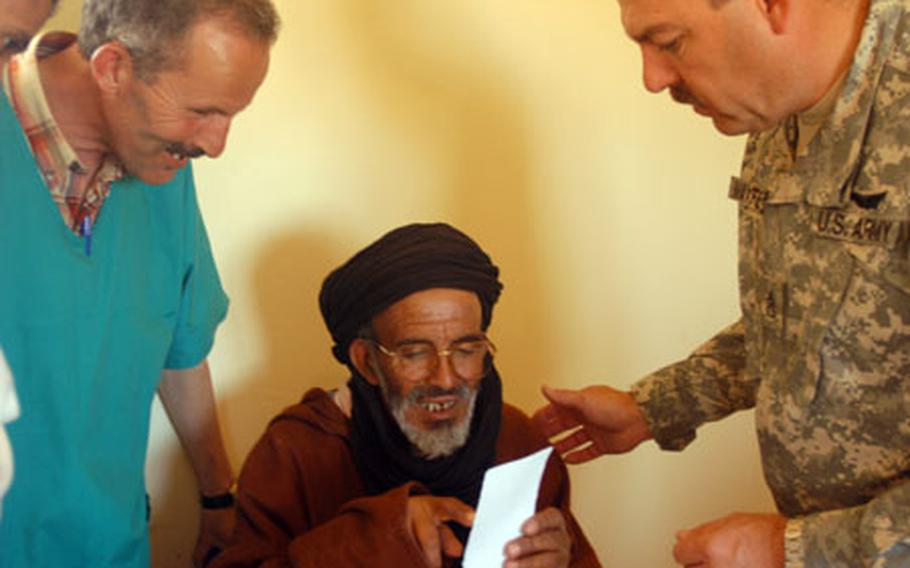 Staff Sgt. Steven Maxfield, right, of the Utah Army National Guard, and Oubaha Mohammed, a local nurse assistant, help a man test some eyeglasses Thursday during a U.S.-Moroccan military medical mission in Ben Khalil, Morocco.