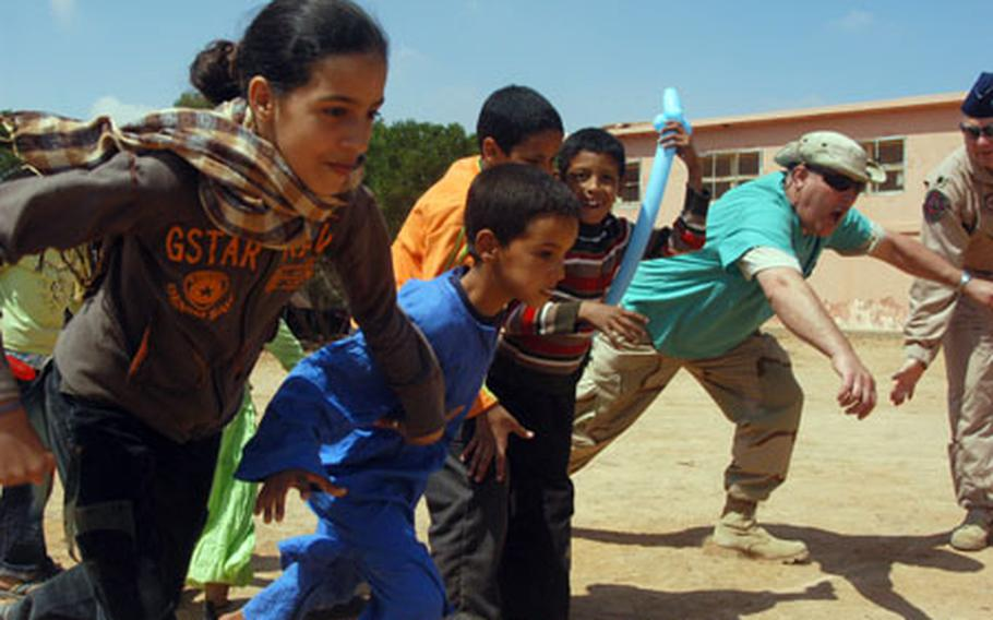 Chief Master Sgt. Joe Guimond of the Utah Air National Guard, right, takes off in a race with local youngsters during a humanitarian civil affairs visit Friday to Ben Khalil, near Tan Tan, Morocco. The troops are taking part in African Lion 07, a military exercise in southern Morocco.