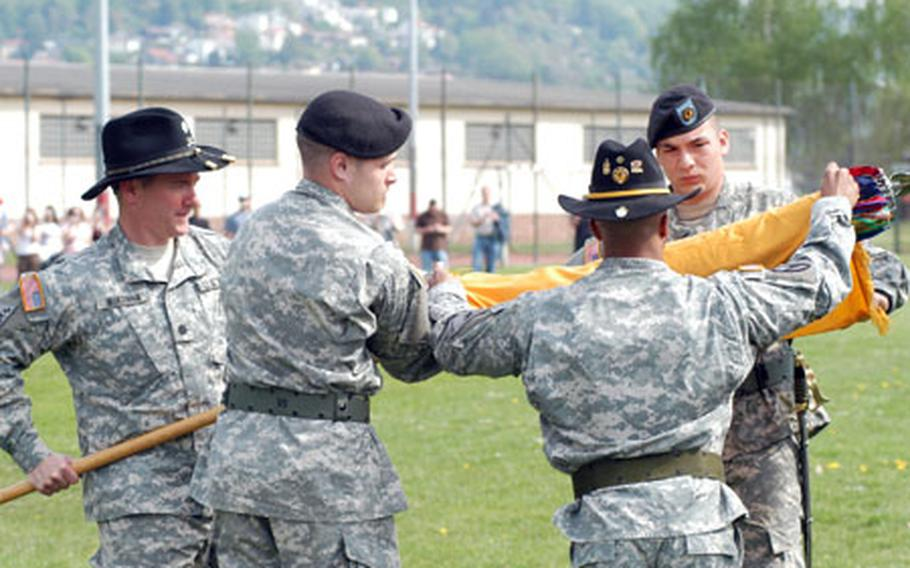 Lt. Col. Matthew McKenna, commander of the 1st Squadron, 1st Cavalry Regiment, holds the staff as Pfc. Richard Saber, center left; Master Sgt. Sheldon Griffin, acting command sergeant major (back to camera); and Pfc. Chad Espinosa roll the colors during the unit's inactivation ceremnoy Tuesday at Armstrong Barracks in Büdingen, Germany.